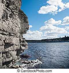rock and river on background of blue sky