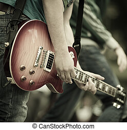 rock and roll - play on guitar, selective focus on part of...