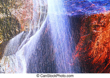 Rock and water - Water flowing down over big granite rock