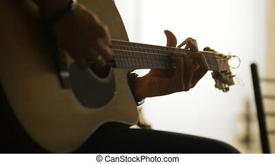 Rock artist playing acoustic guitar at concert in loft or conference hall