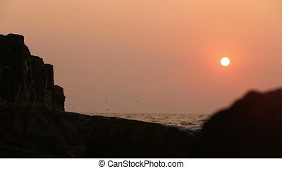 rock at sunset on a background of the sea waves
