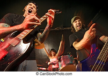 Band playing on a stage. Guitarist, bassist and female drummer. Shot with strobes and slow shutter speed to create lighting atmosphere and blur effects. Slight motion blur on performers.