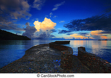 rock bridge into blue sea against beautiful morning light sky an