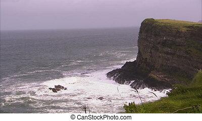 Rock cliffs shoreline - A wide steady shot of waves crashing...