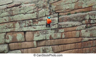 Rock climber - Climber descends down the cliff