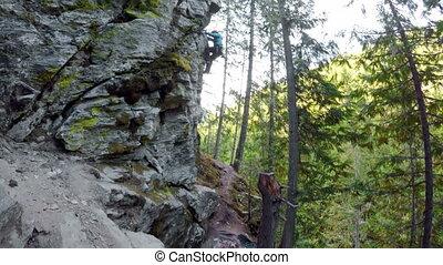 Rock climber climbing a cliff 4k - Rock climber climbing a...