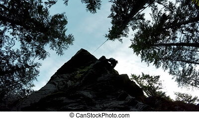 Rock climber climbing a cliff in the forest 4k - Low angle...