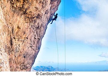 Rock climber climbing up overhanging cliff