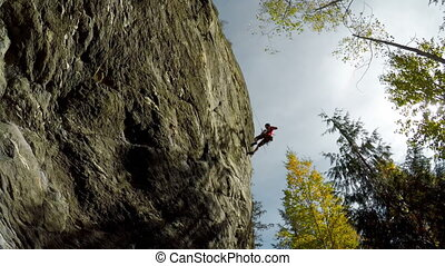 Rock climber descending down the cliff in forest 4k - Low...