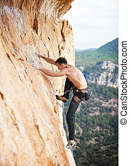Rock climber on a face of a cliff - Young male rock climber...