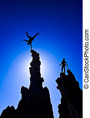 Rock climber celebrates with a handstand on the summit of a pinnacle after a successful ascent.