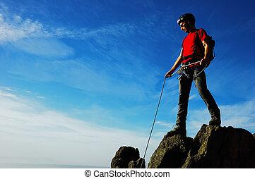 Rock climber, partial cloudy sky, horizontal orientation
