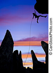 Rock climber rappelling. - A climber is silhouetted as she...