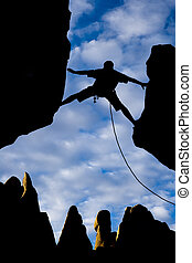 A climber is silhouetted as he reaches across a gap in the rock, in the Sierra Nevada Mountains, California.