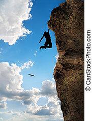 Rock Climber - rock climber climbs the steep cliff to the...