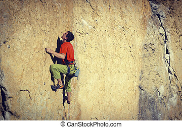 Rock climber. - Rock climber reaching for his next hand...