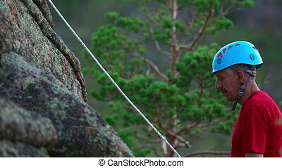 Rock climber - Climber rises upwards on a rock