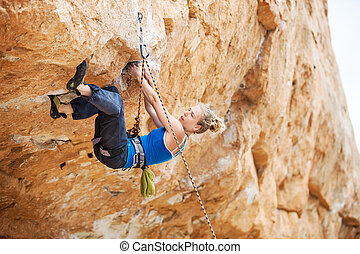 Rock climber struggling to make next movement up - Young...