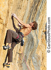 Rock climber struggling to take next handhold