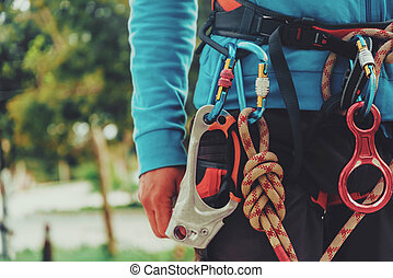 Rock climber wearing safety harness and climbing equipment ...