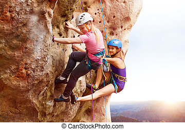 Rock climbers reaching the summit of a mountain