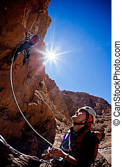 Rock climbing - A female climber belays the leader during a ...