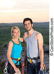 Rock climbing active couple on top sunset - Active young ...