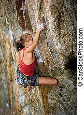 Rock Climbing - An eager female climber on a steep rock face...