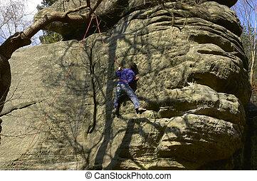 rock climbing - climber climbing a rock face