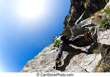 Rock climbing: climber on a steep wall. Clear sky, day...