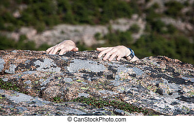 Rock Climbing - Fingers cling to rock in Acadia national...