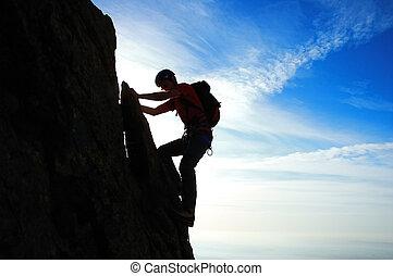 ROCK-CLIMBING - Rock climber silhouette, partial cloudy sky,...