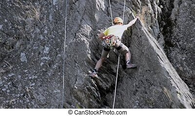 Rock Climbing - Young man climbing up a vertical cliff, seen...