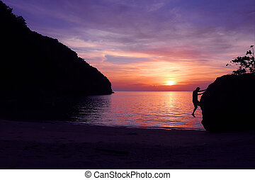 Rock climbing with sunset on the beach.