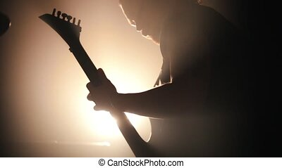 A man playing the guitar in the club. Bright back lighting