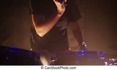 A man plays drums for a rock band performance at the club