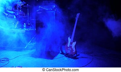 Rock concert background. Electro guitar left on the stage. Smoke at the concert. Music lights at nightclub, concert, festival. Concert concept. Rock concert background. Recording studio advertising