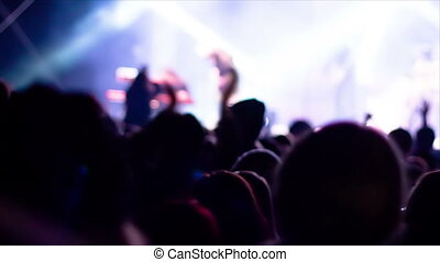 De-focused footage of young people dancing at rock festival concert