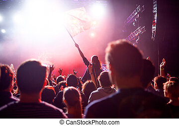 Rock concert, people in the hall on the background of the stage and spotlights.