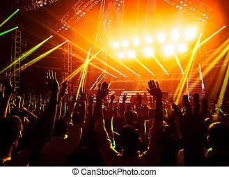 Photo of young people having fun at rock concert, active lifestyle, fans applauding to famous music band, nightlife, dj on the stage in the club, crowd dancing on dancefloor, night perfomance