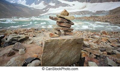 Inukshuk, a rock formation, in front of Angel Glacier, glacial melt, dolly shot