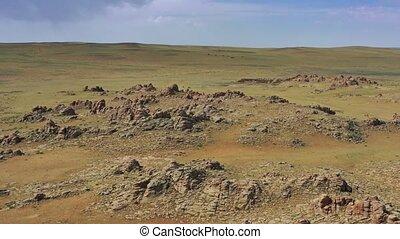 Aerial around view on rock formations and steppe, Baga Gazriin Chuluu, Gobi desert, Mongolia, 4k