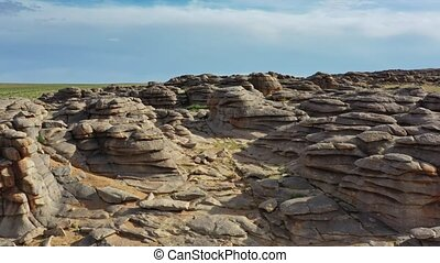 Aerial view on rock formations and stacked stones on granite hilltops, Baga Gazriin Chuluu, Gobi desert, Mongolia, 4k
