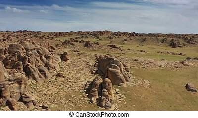 Aerial view on rock formations and stone house in Baga Gazriin Chuluu, Gobi desert, Mongolia, 4k