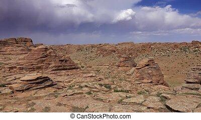 Rock formations and stacked stones on granite hilltops, Baga Gazriin Chuluu, Gobi desert, Mongolia, panorama 4k
