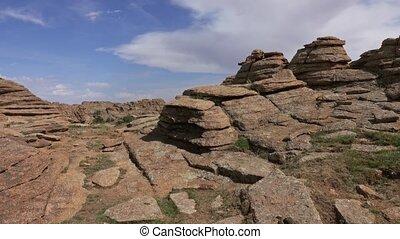 Walking between rock formations and stacked stones on granite hilltops, Baga Gazriin Chuluu, Gobi desert, Mongolia, 4k