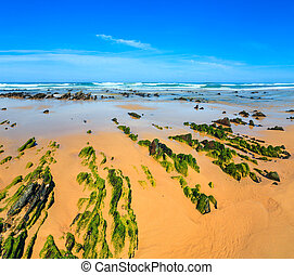 Rock formations on sandy beach (Portugal). - Rock formations...