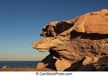 Rock formations on the beach at sunset