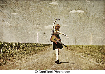 Rock girl with guitar at countryside. Photo in old image style.
