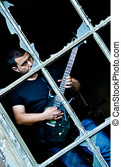 Rock guitarist - Young man playing guitar in front of a...